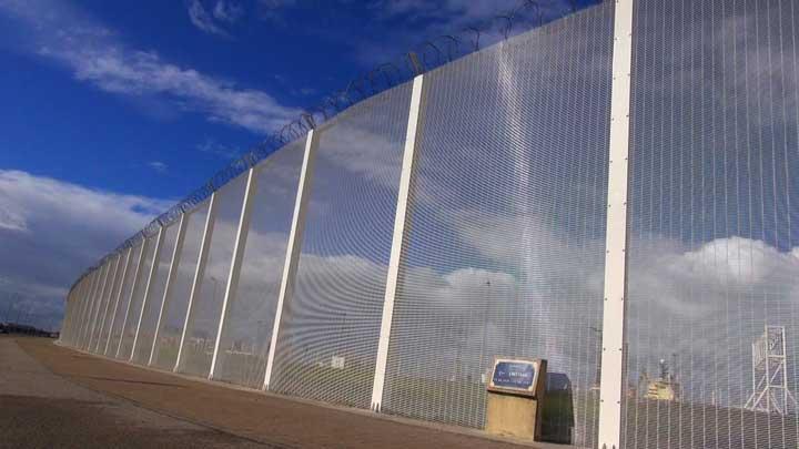 """Une barrière de sécurité entourant le port de Calais près de """"La Jungle"""" (VOA/Nicolas Pinault)"""
