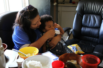 Alondra Ruiz feeds her grandson Gregory while visiting with Win La Bar's family during afternoon practice pick-up. Phoenix, Arizona, Sept. 18, 2015. (VOA/Victoria Macchi)