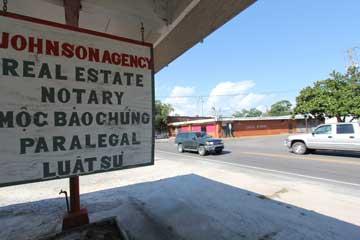 Trên đại lộ Wintzell, một quảng cáo công chứng bằng nhiều ngôn ngữ trên đường phố đối diện một cửa hàng bán thức ăn châu Á và một quán billard đóng cửa. Bayou la Batre, Alabama, ngày 31 tháng 8 năm 2015. (VOA Photo/Victoria Macchi)