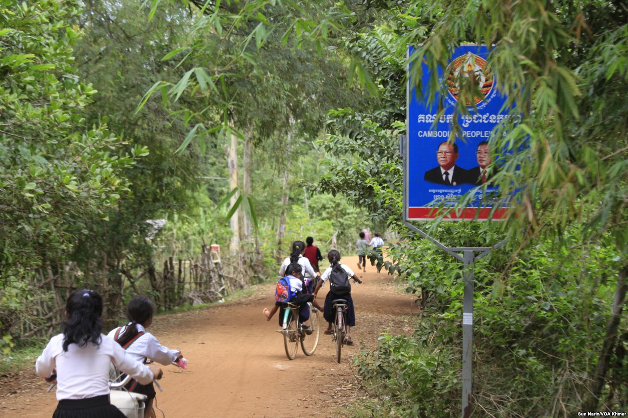 Children ride their bicycles past a sign bearing the Cambodian People's Party logo and the faces of Prime Minister Hun Sen and National Assembly President Heng Samrin