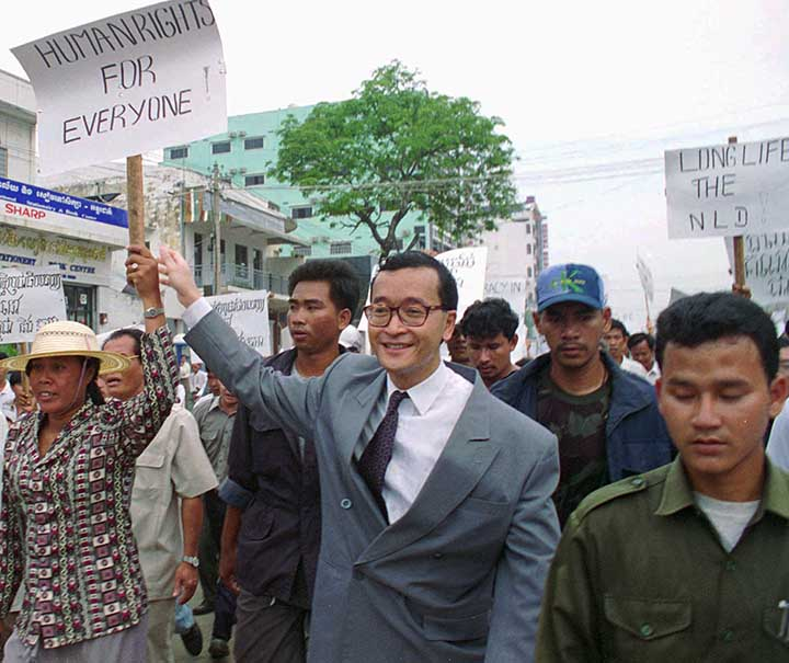 Sam Rainsy marches with protesters carrying signs that read, 'Human rights for everyone.'