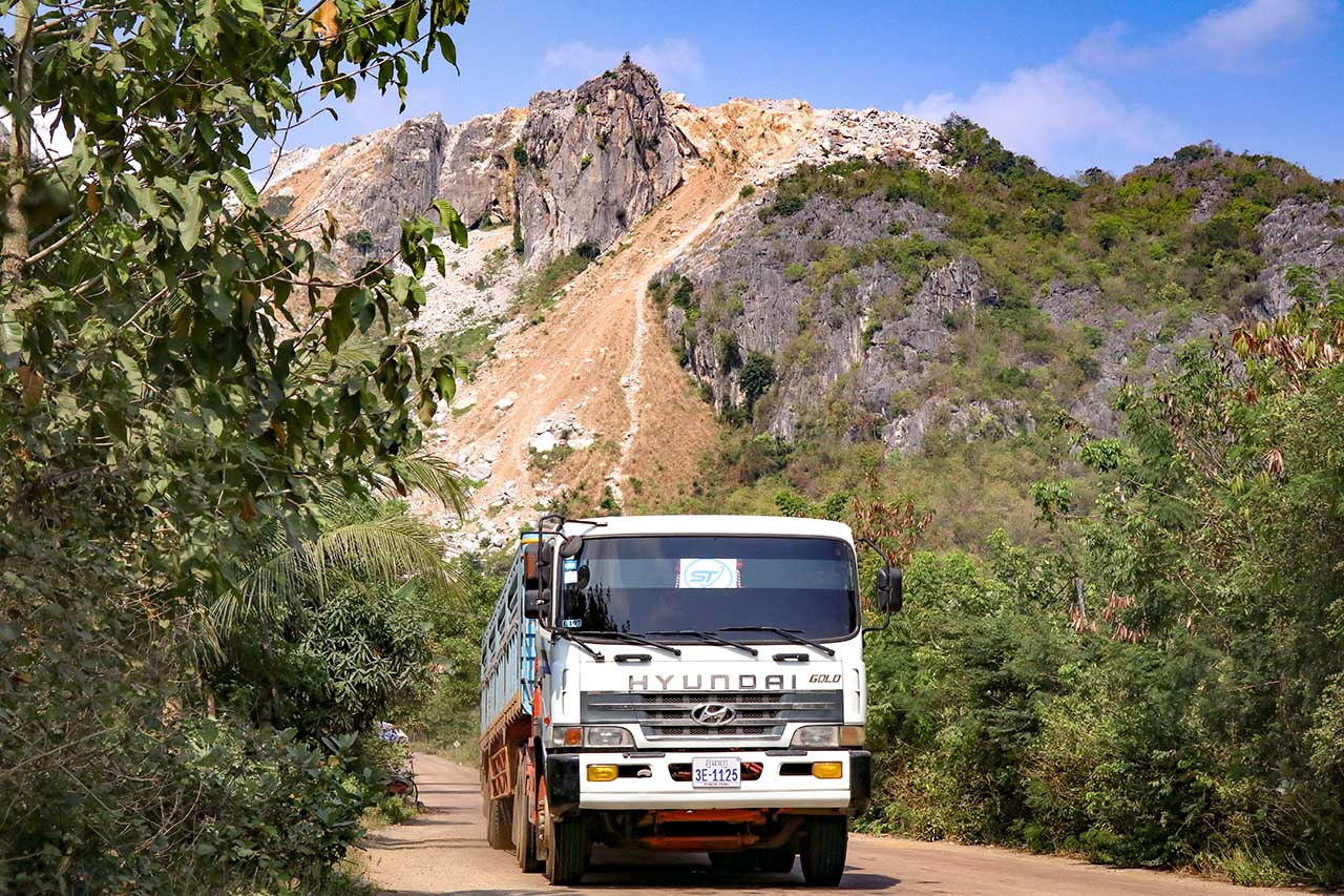 A truck transporting K-Cement passes through the road leading up to Totung Mountain