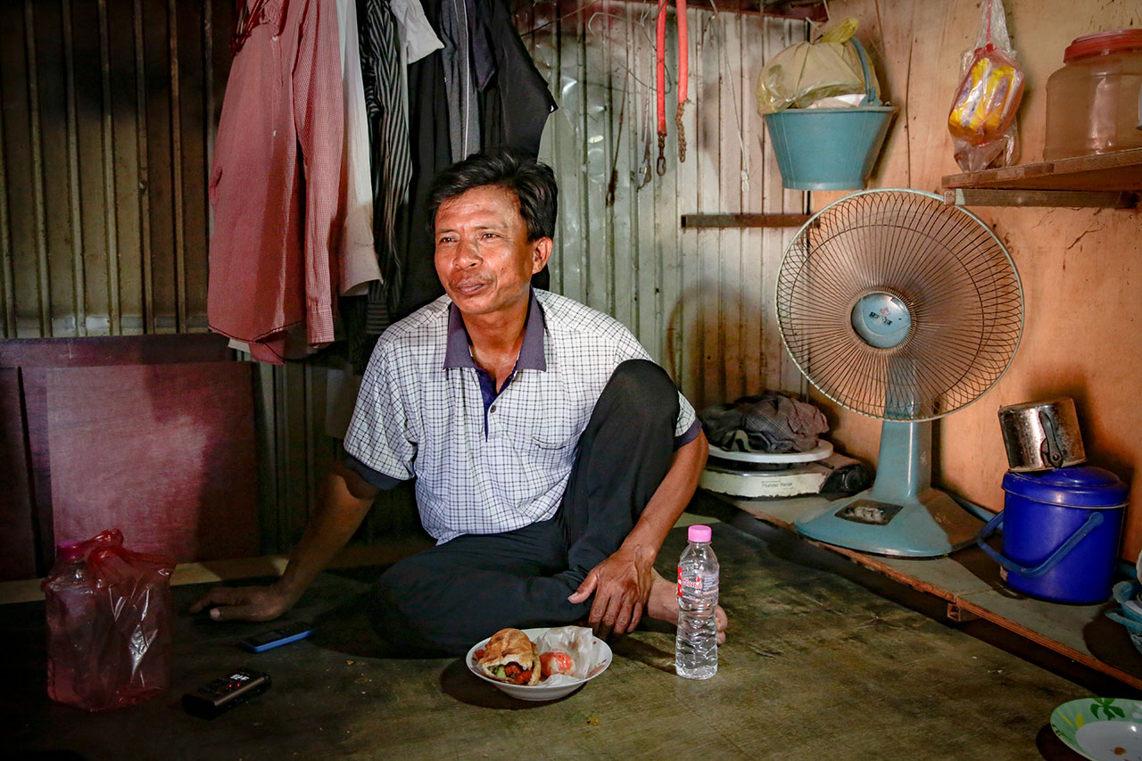 Lounh Bunthoen sitting on the floor in his hut, eating a meal.