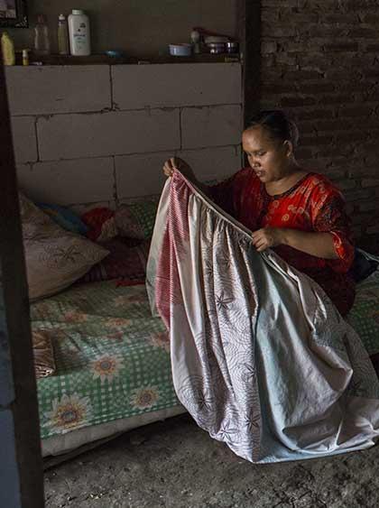 Photo of Rasminah folding a sheet while sitting on a mattress.
