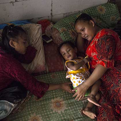 Photo of Rasminah resting on a mattress with two of her daughters.