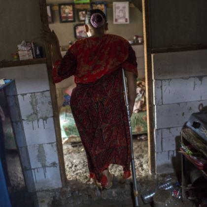 Photo of Rasminah standing in a doorway between the kitchen and the bedroom.