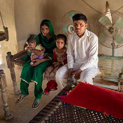 Photo of Qubra sitting with her husband, Dodo Khan, and their son and daughter.
