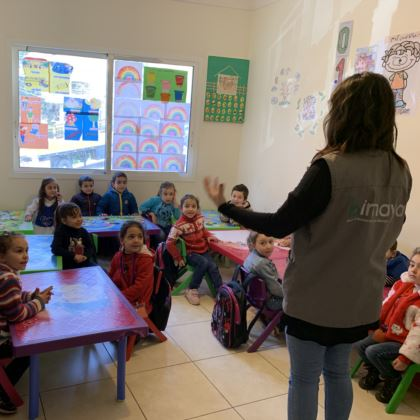 Photo of Syrian children in a classroom listening to a teacher.
