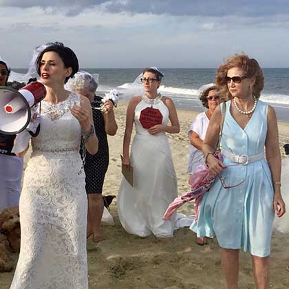 Photo of Fraidy Reiss, left foreground, carrying a megaphone and leading activists wearing wedding gowns across a beach.