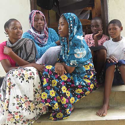 Photo of Mwahanamisi Abdallah, center, sitting on steps with four other girls.