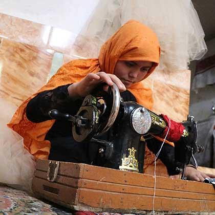 Photo of Somaya sewing on a sewing machine