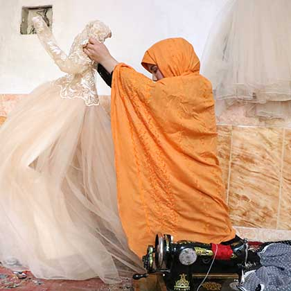 Photo of Somaya unfurling a wedding dress she had sewn.