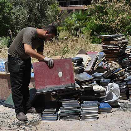 A volunteer stacks historical books rescued from the ashes of Mosul University's destroyed Central Library in an area behind the building before being transported to a safer location.