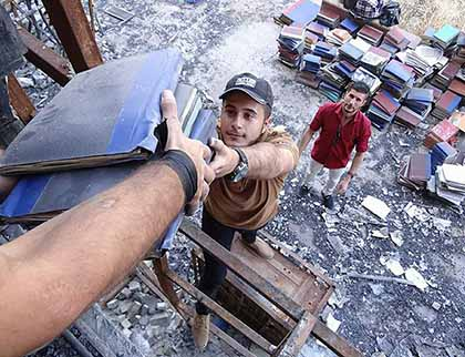Mosul's young volunteers moved dozens of books from inside Mosul University's destroyed Central Library to an area outside the building.