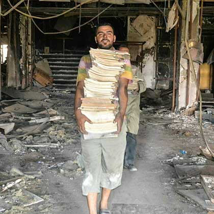 A volunteer carries dozens of books from inside Mosul University's destroyed Central Library.